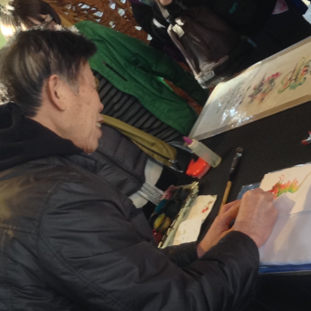 A man demonstrating how to draw with water colors and a bamboo brush.